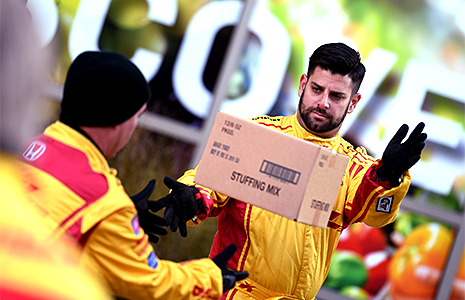 Andretti Autosport crew member Brad Redman tosses a box of stuffing.