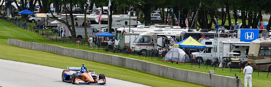 Scott Dixon drives past row of Road America campers