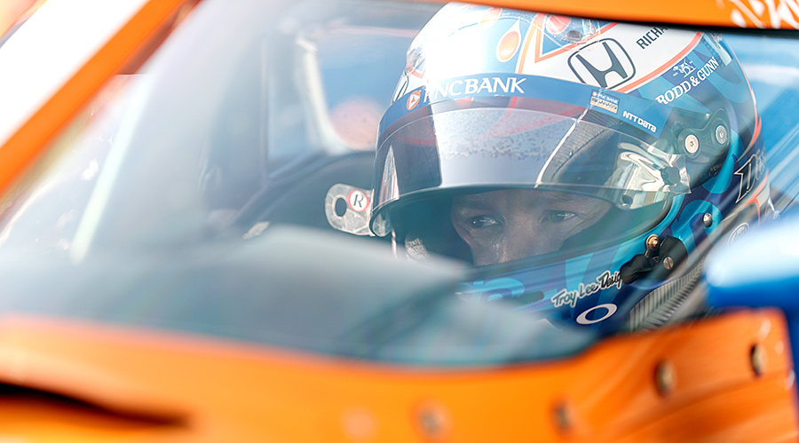 Scott Dixon sitting in his car at Indianapolis Motor Speedway.