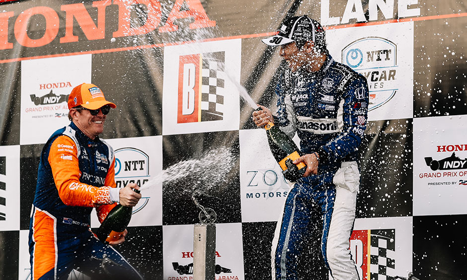 Scott Dixon sprays champagne on Takuma Sato