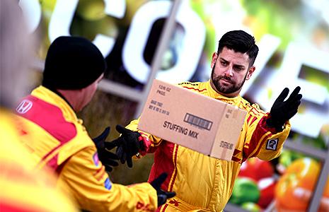 Andretti Autosport crew member Brad Redman tosses a box of stuffing.