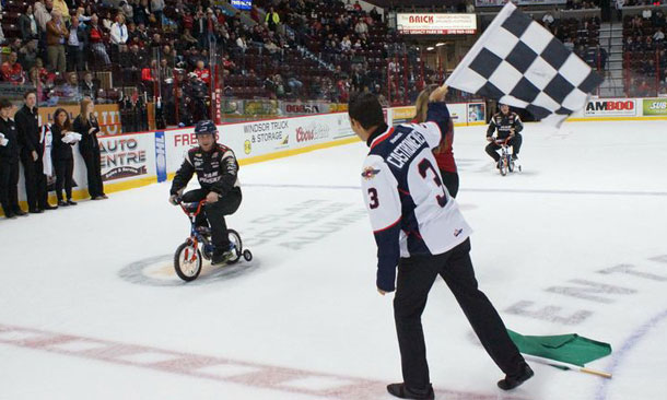 Helio Castroneves waves the checkered flag at Windsor Spitfires game